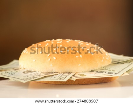 Concept image for rich and greedy. US dollar bills stuffed between burger buns. Burger is placed on a white desk with a brown vignetted background. - stock photo