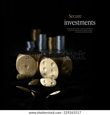 Concept image for secure financial planning. Creatively lit, stacked generic gold and silver coins representing client investment or savings with dice representing risk. Copy space. - stock photo