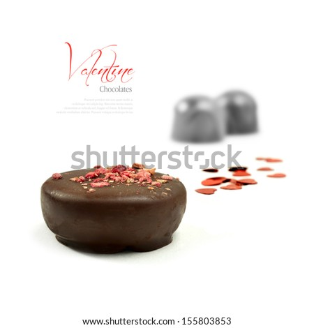 Concept image for Valentines Day. Luxury chocolates with scattered red heart shaped glitter on a white surface against a white background. Copy space. - stock photo