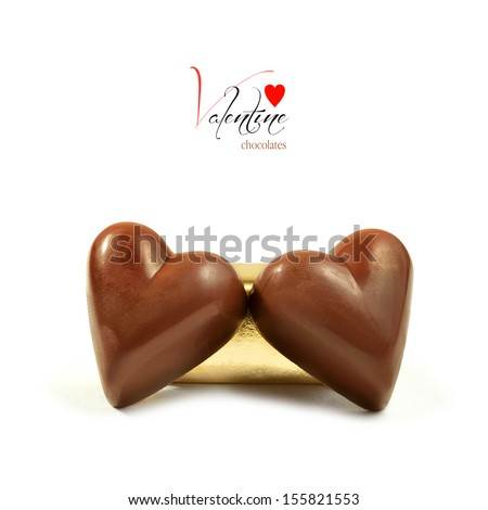Concept image for Valentines Day. Luxury heart shaped chocolates on a white surface against a white background. Copy space. - stock photo