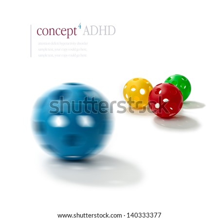 Concept image illustrating Attention Deficit Hyperactivity Disorder (ADHD). Spinning  plastic ball with illusion of two eyes and a mouth in foreground with normal balls in background. ADHD concept. - stock photo