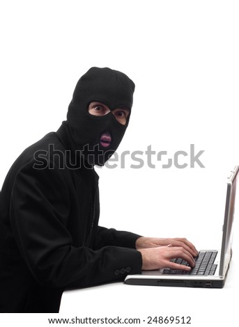 Concept image of a businessman wearing a black balaclava stealing company information - stock photo