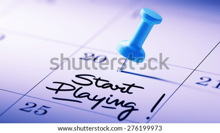 Concept image of a Calendar with a blue push pin. Closeup shot of a thumbtack attached. The words Start Playing written on a white notebook to remind you an important appointment. - stock photo
