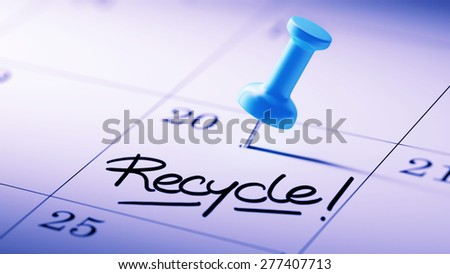 Concept image of a Calendar with a blue push pin. Closeup shot of a thumbtack attached. The words Recycle written on a white notebook to remind you an important appointment. - stock photo