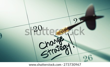 Concept image of a Calendar with a golden dart stick. The words Change Strategy written on a white notebook to remind you an important appointment. - stock photo