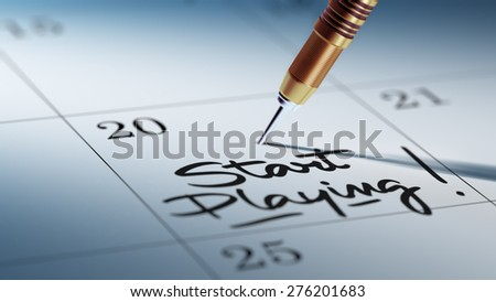 Concept image of a Calendar with a golden dart stick. The words Start Playing written on a white notebook to remind you an important appointment. - stock photo
