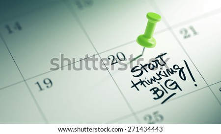 Concept image of a Calendar with a green push pin. Closeup shot of a thumbtack attached. The words Start thinking BIG written on a white notebook to remind you an important appointment. - stock photo