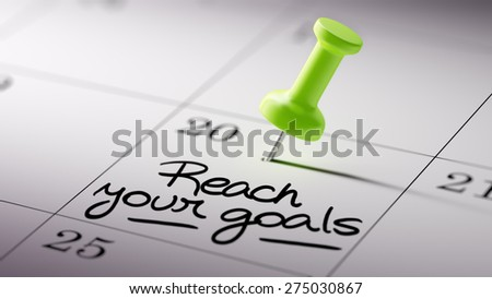 Concept image of a Calendar with a green push pin. Closeup shot of a thumbtack attached. The words Reach your goals written on a white notebook to remind you an important appointment. - stock photo