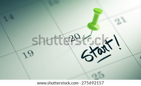 Concept image of a Calendar with a green push pin. Closeup shot of a thumbtack attached. The words Start written on a white notebook to remind you an important appointment. - stock photo