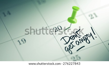 Concept image of a Calendar with a green push pin. Closeup shot of a thumbtack attached. The words Don't get angry written on a white notebook to remind you an important appointment. - stock photo