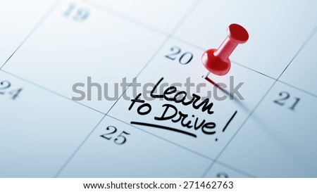 Concept image of a Calendar with a red push pin. Closeup shot of a thumbtack attached. The words Learn to Drive written on a white notebook to remind you an important appointment. - stock photo