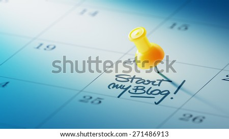 Concept image of a Calendar with a yellow push pin. Closeup shot of a thumbtack attached. The words Start my Blog written on a white notebook to remind you an important appointment. - stock photo