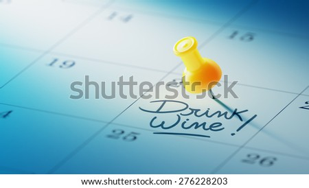 Concept image of a Calendar with a yellow push pin. Closeup shot of a thumbtack attached. The words Drink Wine written on a white notebook to remind you an important appointment. - stock photo