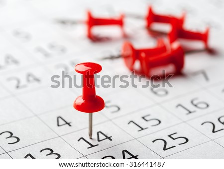 Concept image of a calendar with red push pins - stock photo