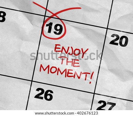 Concept image of a Calendar with the text: Enjoy the Moment - stock photo