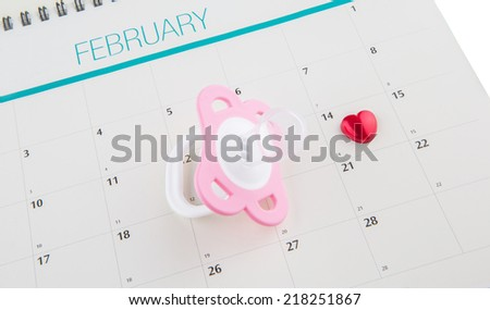 Concept image of baby girl pregnancy delivery due date with calendar page and pink pacifier. - stock photo