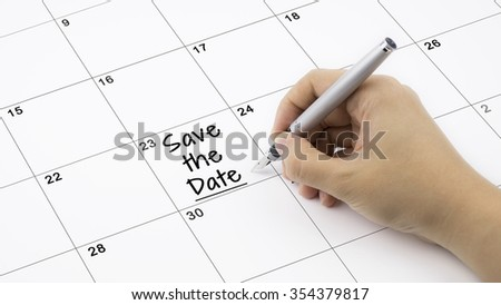Concept image of calendar with a woman hand writing. Words Save The Date written on calendar to remind you an important appointment. - stock photo