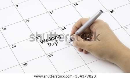 Concept image of calendar with a woman hand writing. Words Wedding Day written on calendar to remind you an important appointment. - stock photo
