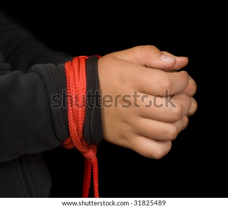 Concept image of child abuse featuring a young girls hands tied with red rope - stock photo