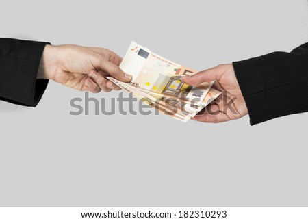 Concept image of hands making and receiving a payment, isolated over a gray background - stock photo