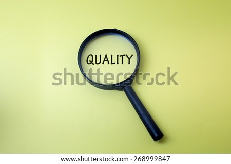 Concept image of magnifying glass showing the QUALITY word - stock photo