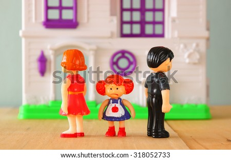 concept image of parent busy or angry and child in the middle in front of. little plastic toy dolls (male , female, child) , selective focus. - stock photo