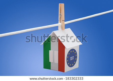 concept - Italy, Italian and EU flag painted on a paper house hanging on a rope - stock photo
