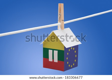 concept - Lithuania, Lithuanian and Euoropean flag painted on a paper house hanging on a rope - stock photo