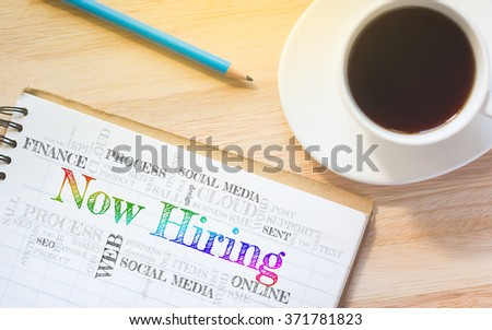 Concept Now Hiring message on book. A pencil and a glass coffee table.Vintage tone. - stock photo