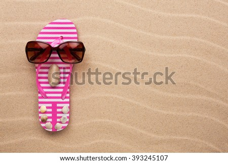 Concept of a woman's face, flip-flops and sunglasses on wavy in sand - stock photo