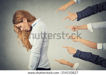 Concept of accusation guilty businesswoman person. Side profile sad upset woman looking down many fingers pointing at her isolated grey office background. Human face expression emotion feeling  - stock photo