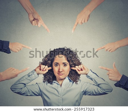 Concept of accusation of guilty businesswoman. Portrait unhappy sad upset woman plugging her ears many fingers pointing at her isolated grey office background. Human face expression emotion feeling - stock photo