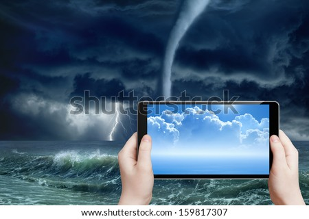 Concept of augmented reality, weather forecast - abstract tablet pc in hands, sunny weather, stormy weather, tornado on sea, dark stormy clouds, bright lightning - stock photo
