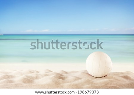 Concept of beach volleyball with ball on sand, blur sea as background - stock photo