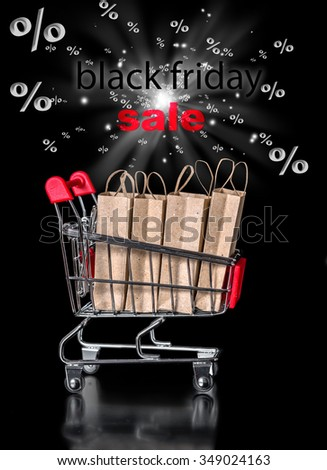 concept of black friday shopping cart with paper bags percent is isolated on black background - stock photo