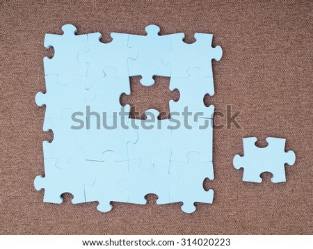 Concept of blue puzzle pieces on the brown background  - stock photo