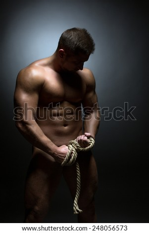 Concept of bodybuilding. Nude man with torn rope - stock photo