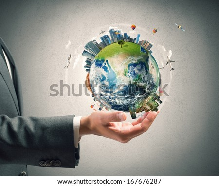 Concept of business power. Businessman holds modern World. World provided by nasa - stock photo
