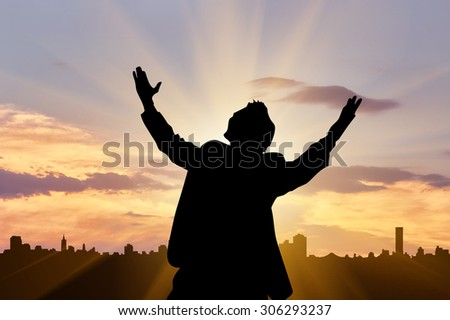 Concept of business. Silhouette of a businessman on the background of the city and night sky with sun rays - stock photo
