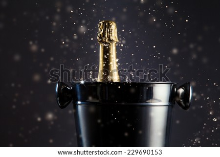 Concept of celebration. Unopened bottle of champagne in metal container - stock photo
