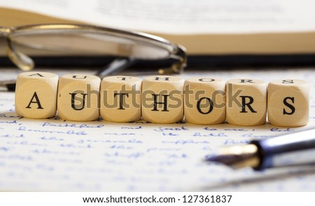 Concept of dices with letters forming words: Authors. Generic handwritten text, pen, glasses and books as background.  Dices made from wood with natural imperfections. - stock photo