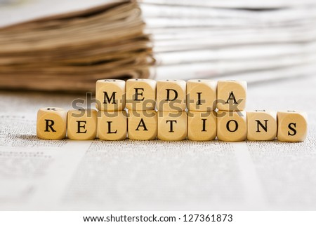 Concept of dices with letters forming words: Media Relations. Generic newspaper background with some blurred text on the bottom and paper stack in the back. - stock photo