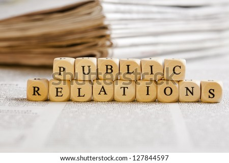 Concept of dices with letters forming words: Public Relations. Generic newspaper background with some blurred text on the bottom and paper stack in the back. - stock photo
