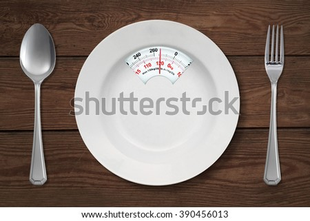 Concept of diet. Close up of empty plate shaped a scale with spoon and fork on the wooden table - stock photo