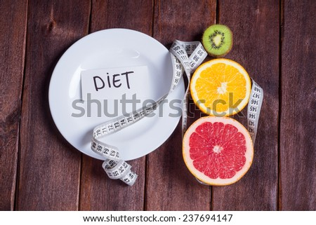 Concept of diet. Low-calorie fruit diet. Diet for weight loss. Plate with measuring tape and fruits on the table. Vegetarian diet for weight loss. Wellness. - stock photo