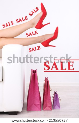 Concept of discount. Beautiful female legs in red shoes on sofa with shopping bags - stock photo