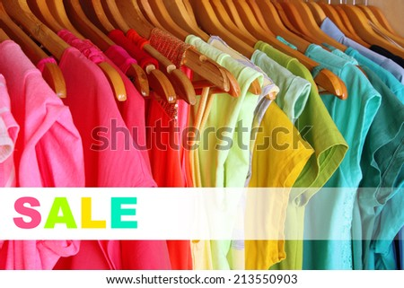 Concept of discount. Colorful clothes on hangers in wardrobe - stock photo