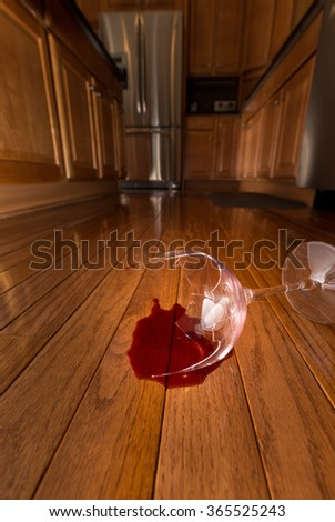 Concept of domestic disturbance at home with broken wine glass on floor of modern kitchen - stock photo