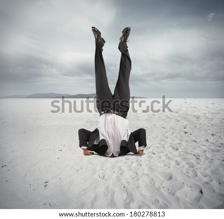 Concept of economic downfall with businessman upside down - stock photo