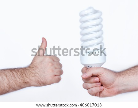 Concept of energy saving, a hand holding a fluorescent lightbulb while another hand showing ok sign, thumbs up - stock photo